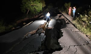 A news cameraman films a damaged road following an earthquake on the outskirts of Mirpur on September 24, 2019.