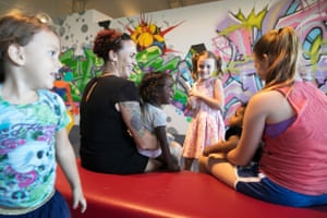 A family enjoys the artwork at Museum and Art Gallery of Northern Territory, which includes a space were visitors can add to walls of graffiti