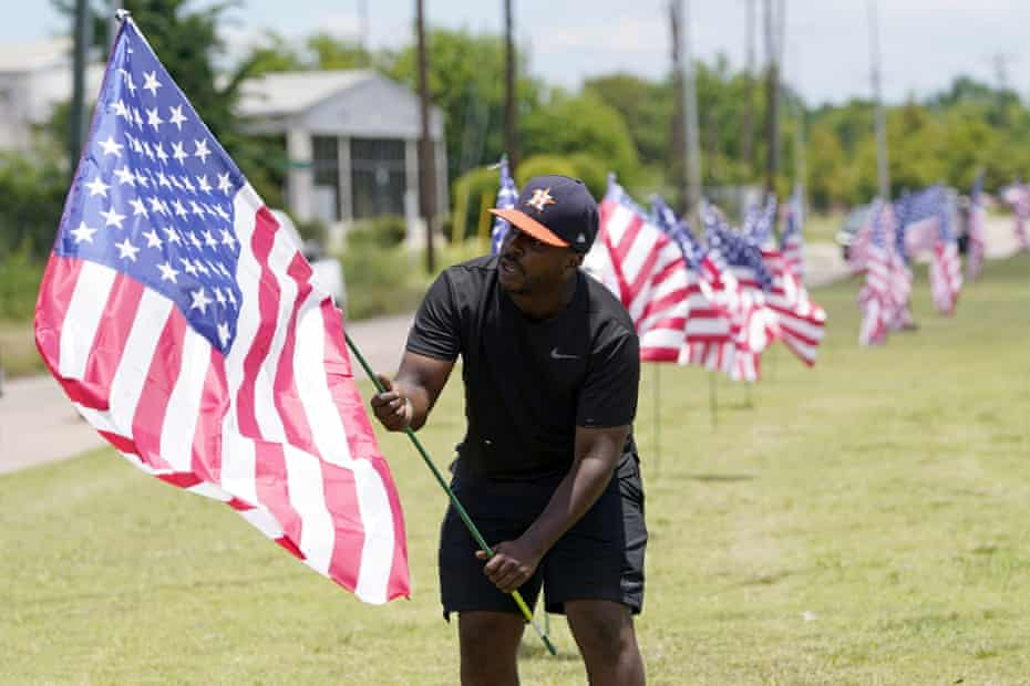 Bryan Smart plants American flags along Hillcroft Avenue as he walks toward The Fountain of Praise church on Sunday in Houston. A public memorial and private funeral service for George Floyd will be held at the church.
