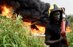 A firefighter works to put out the fire from a ruptured oil pipeline near Lagos.