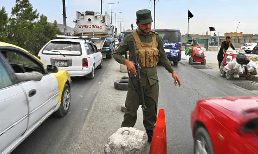 An Afghan policeman stands guard at a checkpoint in Kabul on 14 August.