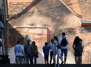 Zagreb, CroatiaTourists walk near an artwork of artist Julien De Casablanca on a building facade. Julien De Casablanca is French and Corsican visual artist and filmmaker who launched Outings Project, which consists in bringing paintings from museum walls into the streets all over the world