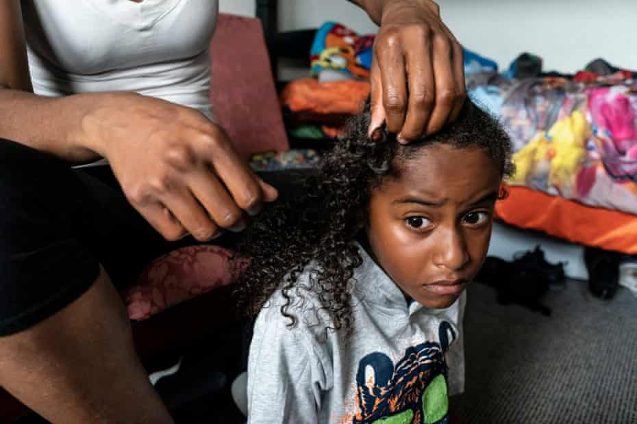 Cherokeena Robinson braids her son Mai'Kel's hair in the morning in their room at their transitional house in San Pedro, California that they share with one or two other families at a time. Cherokeena lost her job during the pandemic and now relies on the organization Family Promise to help with housing, childcare, food, and counseling. Cherokeena and her son have been living in the transitional house since June 2020 where she pays $300 a month for rent for a private room until she can figure out her job and find a full private apartment of her own.