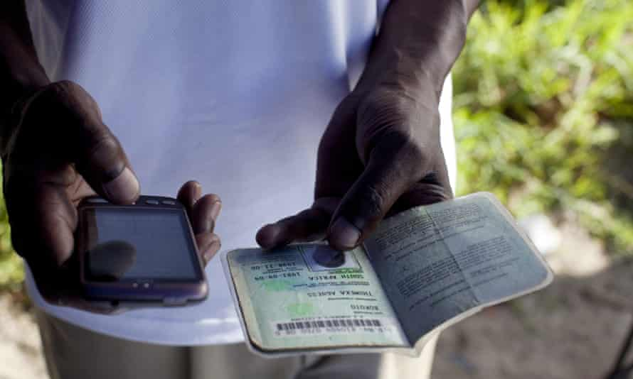 A bank clerk uses a mobile phone to verify a customer's identity document as he sells accounts on a street in Khayelitsha, South Africa.