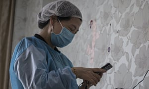 A physiotherapist uses an iPhone in a private obstetric hospital on February 24, 2020 in Wuhan, China.
