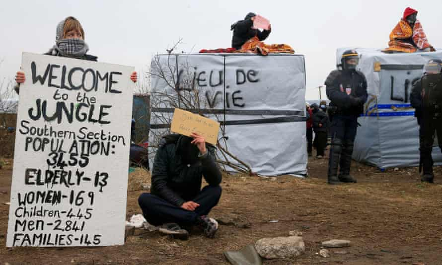 French riot police secure the area as activists and migrants sits on their makeshift shelters in protest.