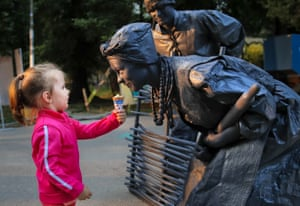 A child offers ice-cream to one of the artists from Ukraine's Artel Myth theatre