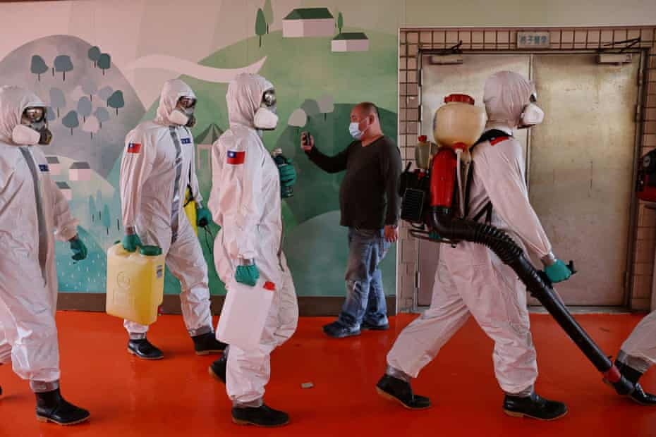 Soldiers prepare to spray disinfectant at the Taoyuan general hospital, where a cluster of Covid-19 infections was detected.