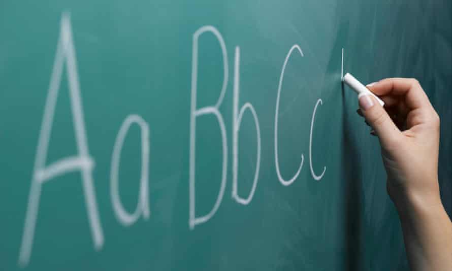 A woman writing the alphabet on chalkboard