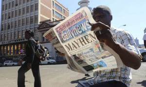 A man reads a newspaper headline in Harare, Zimbabwe, while awaiting the presidential election results.