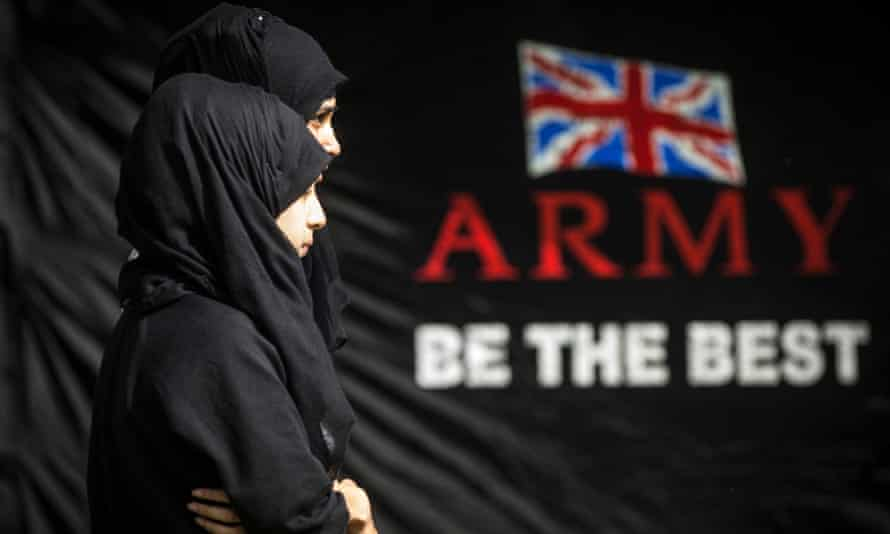 Female Muslim pupils next to a sign that says Army be the Best
