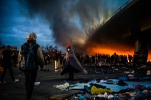 Migrants set fire to their belongings for warmth as they wait to be evacuated by French police at a makeshift migrant camp set under the A1 freeway in Saint-Denis, north of Paris.