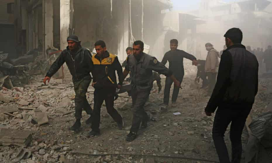 Volunteers from the Syria Civil Defence, known as the White Helmets, carry a victim following a reported air strike in the rebel-controlled town of Hamouria.