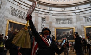 Supporters of Trump enter the US Capitol's Rotunda, with one brandishing a Captain America shield.