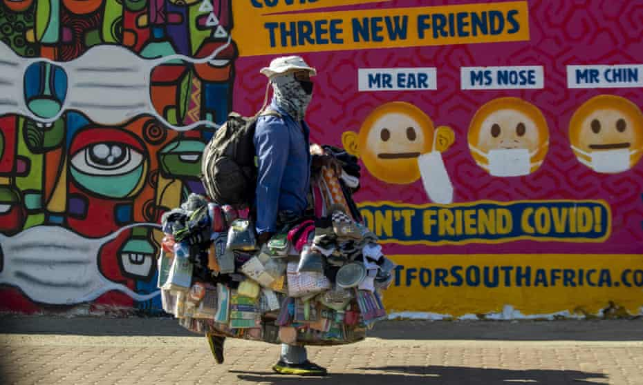 A street vendor walks past a mural on how to prevent the spread of coronavirus in Soweto, South Africa