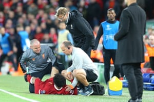 Mohamed Salah is treated and goes off injured as Jurgen Klopp watches.