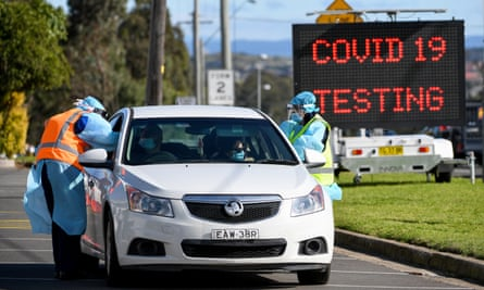 NSW Health workers conduct Covid-19 tests outside the Crossroads Hotel on Thursday, as the cluster at the pub in Sydney's south-west grew to 40 case.
