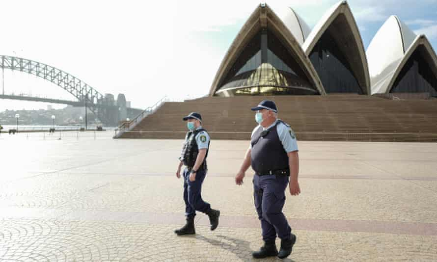 Police officers patrol at the Sydney Opera House amid Covid lockdown.