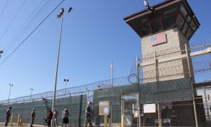 Poeple walk past a guard tower outside the fencing of Camp 5 at the US military's prison in Guantánamo Bay, Cuba.