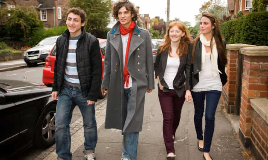 Mixed sex group of teenagers walking along the street in an urban area