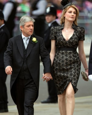 Bercow in morning suit walking holding hands with Sally, much taller than him, wearing fascinator.