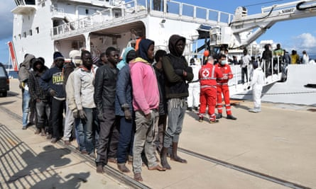 """Migrants and refugees arrive in the port of Messina following a rescue operation at sea by the Italian Coast Guard ship """"Diciotti"""" in 2016 in Sicily."""