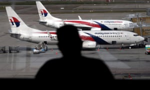 A passenger looks at Malaysia Airline planes from the viewing gallery at Kuala Lumpur International Airport.