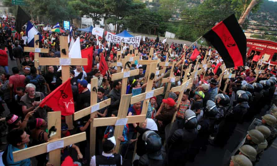 Opposition supporters hold wooden crosses in front of security forces guarding the US embassy during a protest in Tegucigalpa, Honduras Thursday.