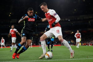 Mesut Ozil shields the ball from Allan of Napoli.