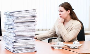 Woman working in office room. Focus on pile of papers