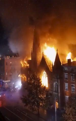 Flames engulf the church, before dawn.