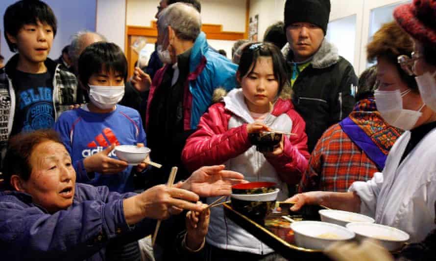 People from the area around the Fukushima plant receive a meal at an evacuation centre in 2011.