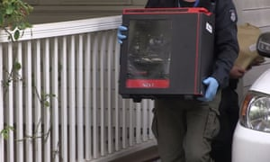 A police officer hauls away a computer during raids across Victoria that uncovered child abuse material.