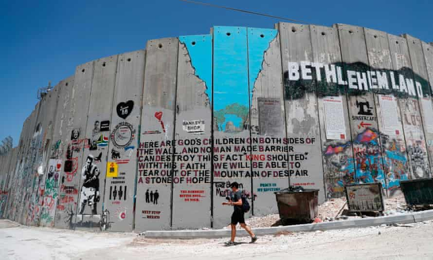A person walks past graffiti in the West Bank city of Bethlehem in 2017