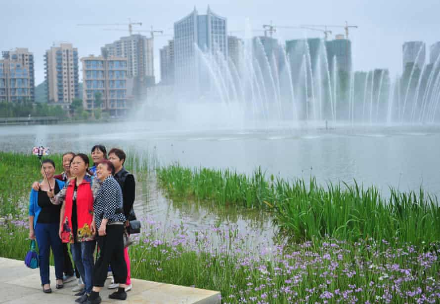 Tourists pose for a photo in Quanhu lake park in Guiyang.