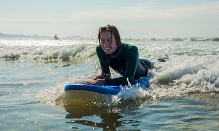 Surfer gliding on ocean wave, Watergate Bay, Cornwall, UKR12DHX Surfer gliding on ocean wave, Watergate Bay, Cornwall, UK