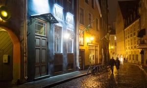 A couple walks past Von Krahl theater at Rataskaevu street by night.