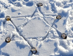 Candles burn in a star of David in the snow at the Nazi concentration camp Buchenwald
