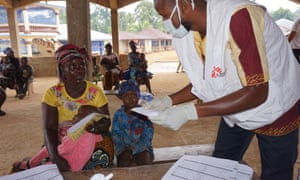 A Médecins Sans Frontières health worker tends to a mother and her child at a mobile clinic in Sierra Leone