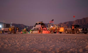 Boeing, NASA, and US Army personnel working around the Boeing CST-100 Starliner spacecraft shortly after it landed in White Sands, New Mexico.
