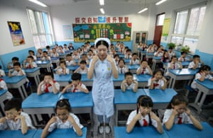 A hospital staff member teaches children eye exercises at a primary school in Handan, Hebei province, China