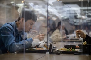 Employees sit behind protective screens in a cafeteria at the offices of Hyundai credit card company in Seoul, South Korea