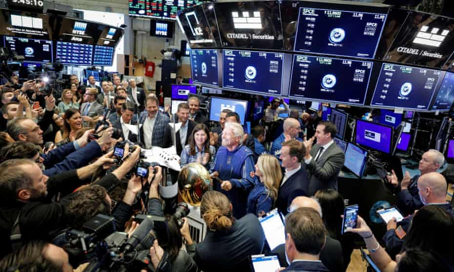 surrounded by a throng of journalists on the floor of the  New York Stock Exchange