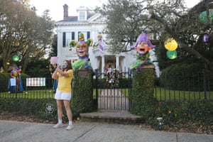 A woman takes a selfie in front of decorations for Mardi Gras