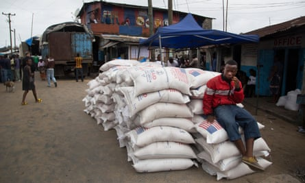 A man sits on top of USAid parcels in West Point, Liberia.