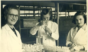 Black and white photo; inside an industrial-looking laboratory, three young women stand around a laboratory bench covered in glassware.  The two to the left and right look out at the camera, while the woman in the centre concentrates on pipetting material into or out of a glass vial.