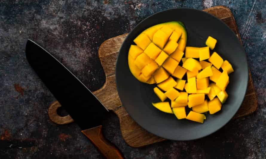 """A """"hedge-hogged"""" mango cheek, with cubes of fruit next to it."""
