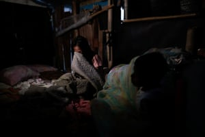 Siblings Cindy, 14, and DJ Martinez, 12, wake up in their bamboo hut which stands on stilts in the submerged coastal village of Sitio Pariahan.
