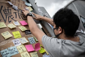 A man glues a sticker on the wall in front of West Kowloon Train station during the protest against the extradition law to China.