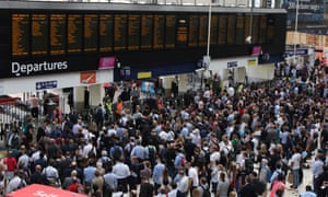 Commuters crowd around departure boards at Waterloo station in London